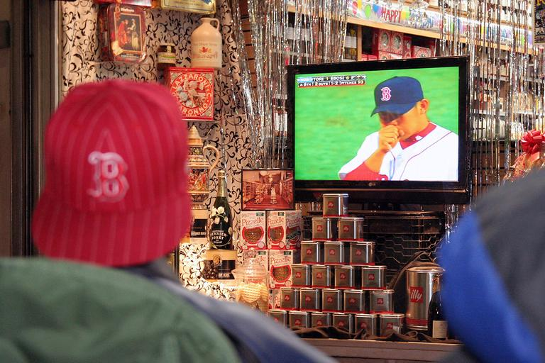 The club members watch the game on the flat screen inside Cardullo's display window. (Andrew Phelps/WBUR)