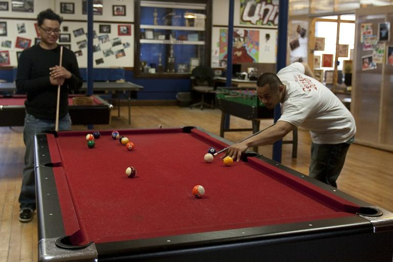 Johnny and Ricky play pool at the United Teen Equality Center in Lowell. (Jess Bidgood for WBUR)