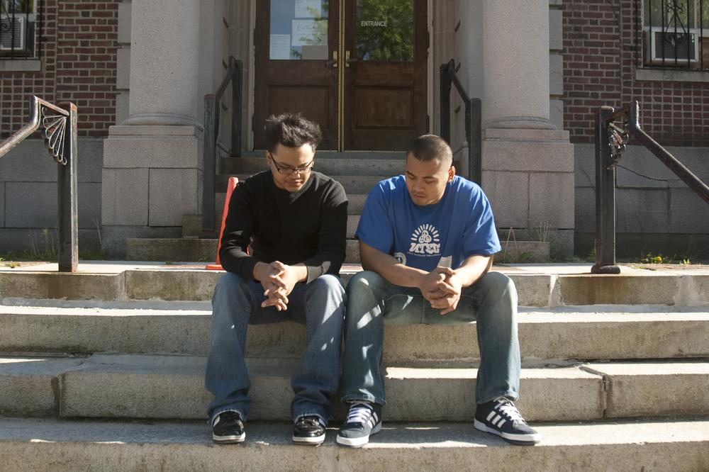 Ricky Le, left, and Johnny Chheng talk on the steps of the Lowell Courthouse. (Jess Bidgood for WBUR)