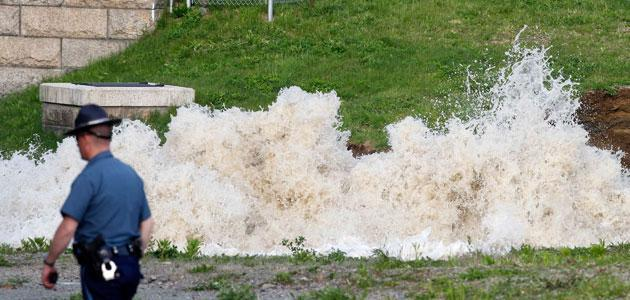Water surged from the ground at the site of a water main break on Saturday in Weston, Mass. (AP)