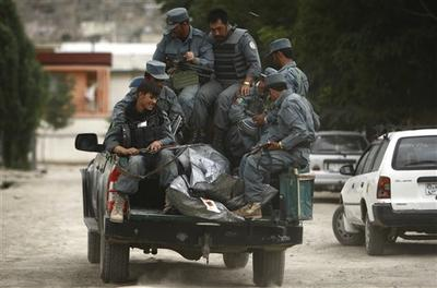 Police officers leave with the two bodies of alleged Taliban militants who were killed in a gunbattle in Kabul, Afghanistan. (AP)