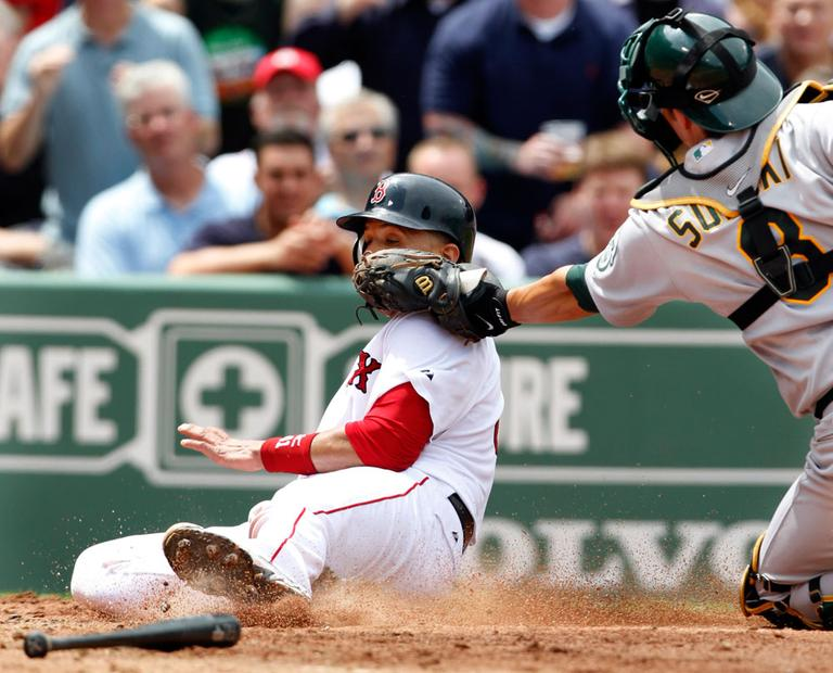 Boston Red Sox's Victor Martinez is out at home while attempting to score on a double hit by Red Sox's Kevin Youkilis as Oakland Athletics' catcher Kurt Suzuki makes the play in the third inning from Fenway Park on Thursday. (AP)