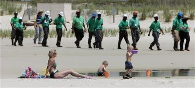 Mary Smith of Theodore, Ala., watches over her grandchildren as a large crew of clean up workers walk along the beach in Dauphin Island, Ala.(AP)