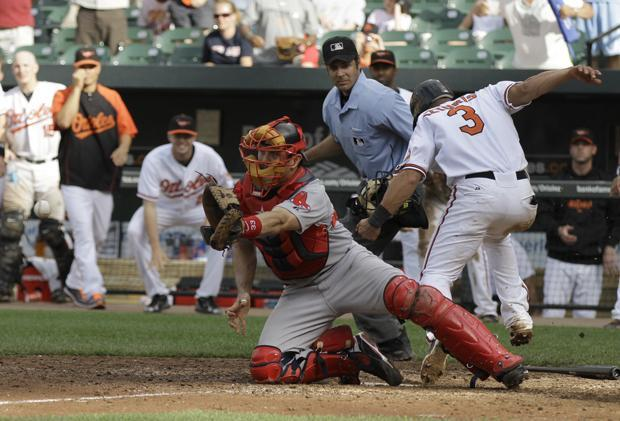Baltimore's Cesar Izturis scores the winning run on a single by Nick Markakis as Boston catcher Jason Varitek waits for the throw at the plate during the 11th inning of the game on Sunday in Baltimore. The Orioles won 4-3. (AP)