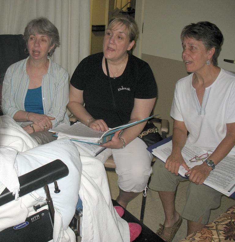 Three members of Threshold Choir sing to 85-year-old Ruth Coleman at a Littleton nursing home. (Monica Brady-Myerov/WBUR)