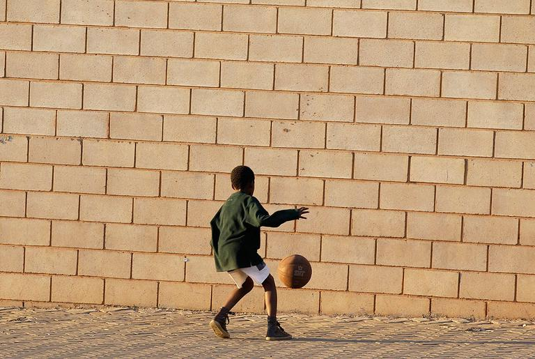 A boy kicks a ball in front of the Super Stadium in Atteridgeville, near Pretoria, South Africa, on Tuesday. The World Cup kicks off for the first time on the continent on Friday. (AP)