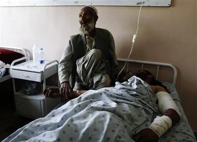 An unidentified father comforts his injured son at a hospital following a blast at wedding party in Kandahar city, Afghanistan, on Thursday. (AP)
