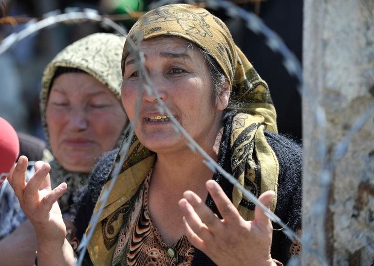 An Uzbek woman who fled from the southern Kyrgyz city of Osh after her husband was killed and house burned down stands in line near the Uzbek village of Jalal-Kuduk waiting for permission to cross into Uzbekistan, on Monday. (AP)