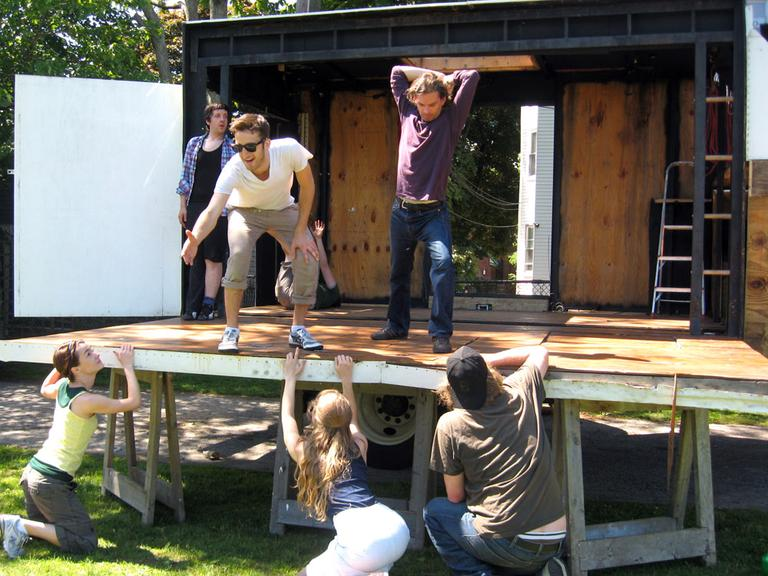 """With """"The Theatre Truck"""" parked and opened, its actors go through a recent rehearsal. (Andrea Shea/WBUR)"""