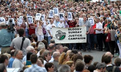 Relatives and families join members of the bogside area holding pictures of victims aloft, as they gather to march to the Guildhall for a preview of the just-released Saville report into the 1972 Bloody Sunday Shootings, in Londonderry, Northern Ireland.(AP)