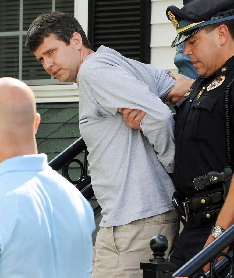 Thomas Mortimer IV is led from the police station by Police Chief James Palmeri after he was arrested Thursday in Bernardston. (AP)