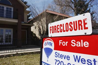 A sign noting the foreclosure status of a single-family home tops the for sale sign in Denver, Co. (AP)