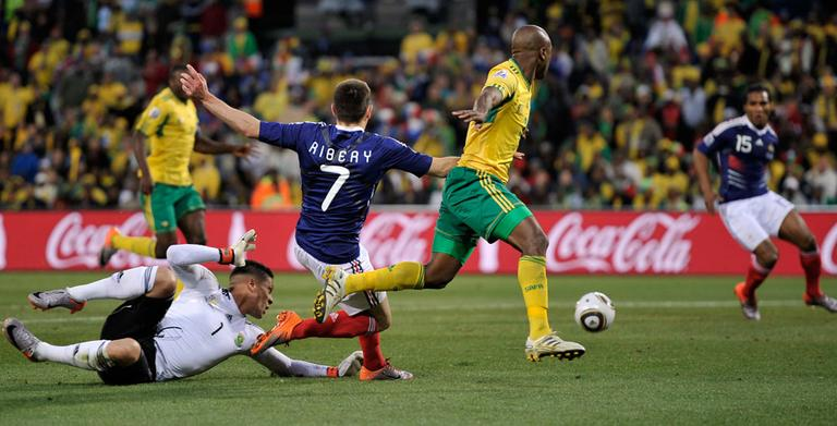 France's Franck Ribery, center, crosses the ball to Florent Malouda, right, to score a goal during a match against South Africa on Tuesday. France lost though, 2-1, and was ousted from the World Cup. (AP)