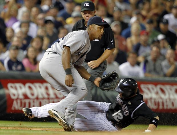 Clint Barmes slides safely into third base while third base umpire Ron Kulpa, back, looks on in the sixth inning of the game in Denver on Thursday. (AP)