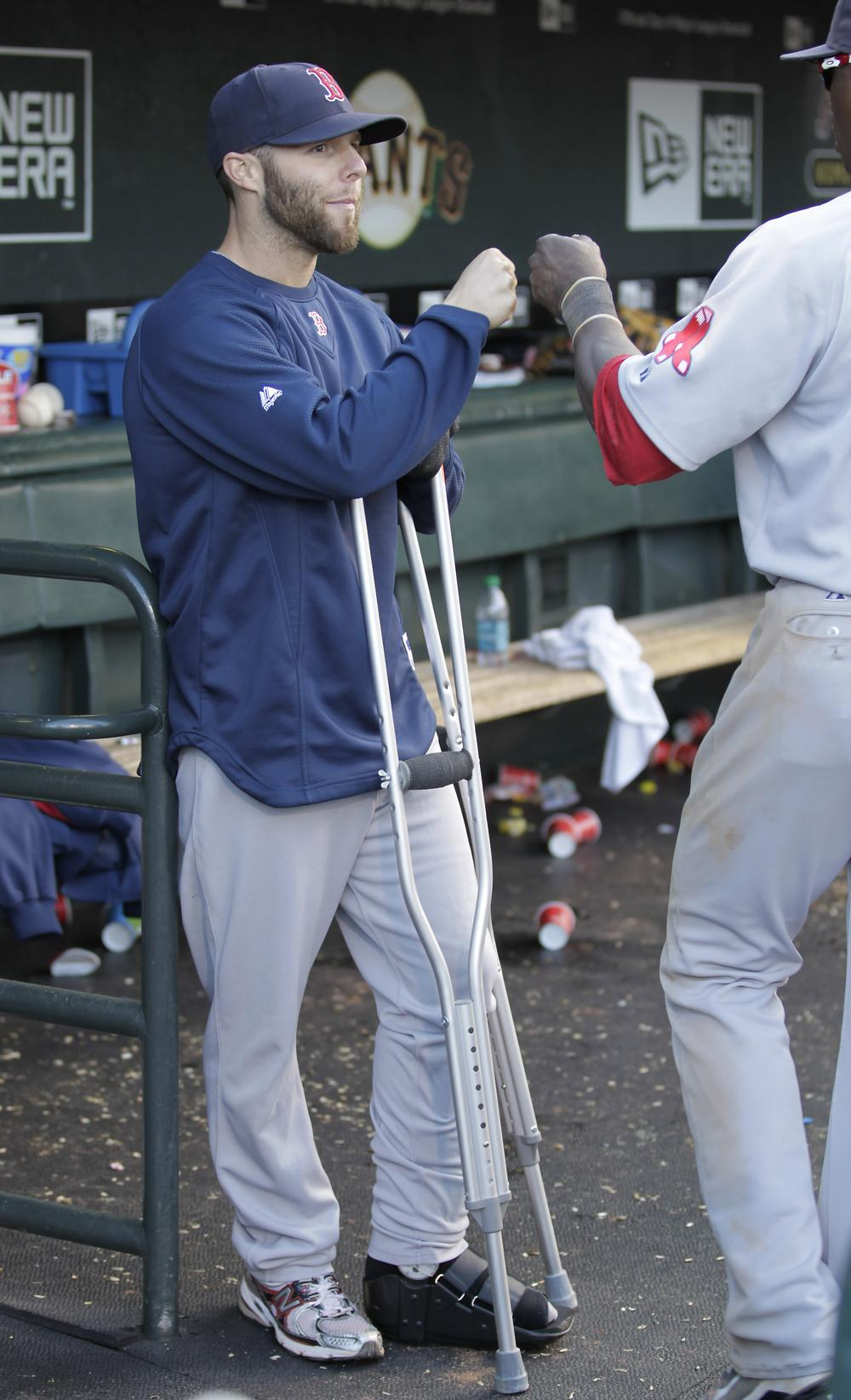 Dustin Pedroia, left, is seen in the dugout on crutches congratulating teammates after a 4-2 victory against the San Francisco Giants on Saturday. (AP)