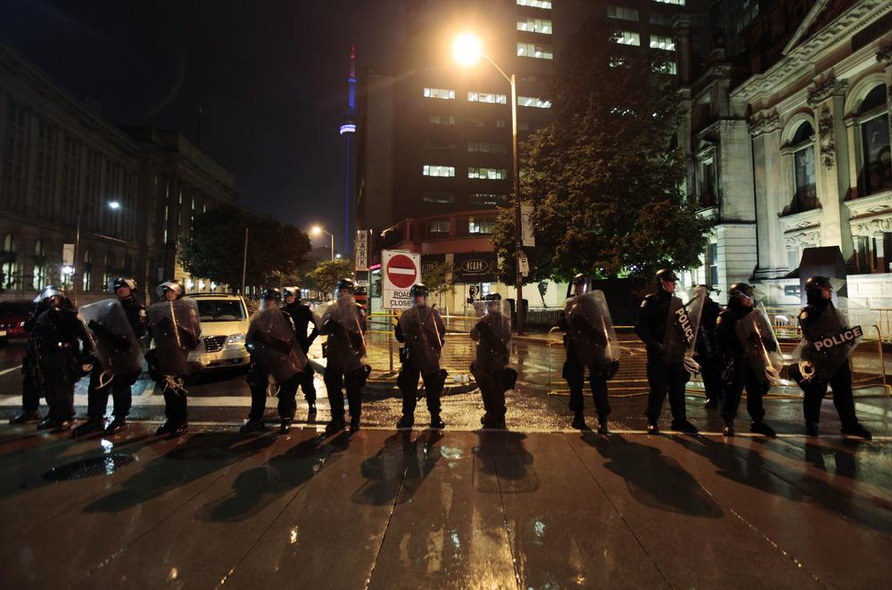 Canadian police officers form a line to prevent demonstrators from near the fence that surrounds the G-20 global economic summit in downtown Toronto, Canada, late Saturday.  (AP Photo/Lefteris Pitarakis)