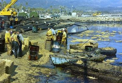 In this 1969 picture, workers use straw to absorb oil from the beach at Santa Barbara Harbor, Calif. The oil which leaked from an offshore well, covered local beaches and threatened many southern California shoreline areas. The incident at the Union Oil Co. platform helped lead to the Clean Water Act. (AP)