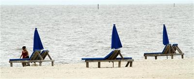Unoccupied umbrellas and lounges along the beach in Biloxi, Miss. (AP )