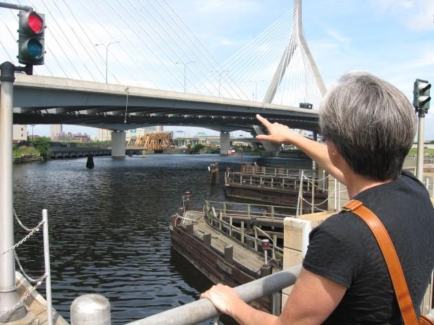 Kate Bowditch, of the Charles River Watershed Association, points to where the river meets Boston Harbor. She hopes public swimming will be possible here some day. (Sacha Pfeiffer/WBUR)