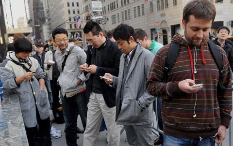 People use mobile devices while waiting in line to purchase the iPad outside the Apple store on Fifth Avenue in New York, April 3, 2010. (AP)