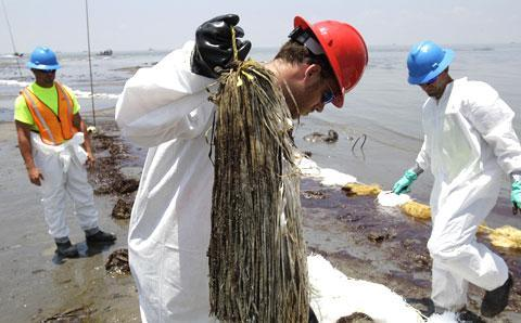 Workers collect snare booms used to remove oil washed ashore from the Deepwater Horizon spill in Belle Terre, La. (AP)