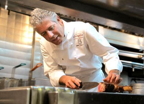 "Anthony Bourdain in his show ""No Reservations"" cutting steak. (Credit: TravelChannel.com)"
