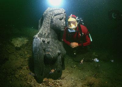 A diver is inspecting a Granite head emerging from the sediment at the Heracleion site. The head belongs to a statue of a Ptolemaic Queen dressed as the Goddess Isis. (Credit: Franck Goddio / Hilti Foundation, Photo: Christoph Gerigk)