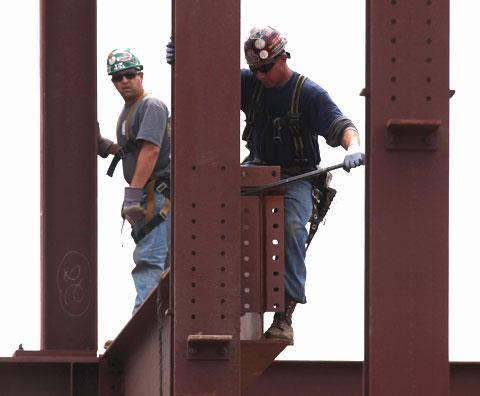 Construction workers guide a steal beam into place on a building in Philadelphia, April 27, 2010 (AP)