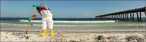 Cleaning up oil washed ashore at Pensacola Beach, Florida, June 23, 2010. (AP)