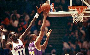 Philadelphia's Manute Bol, left, blocks a shot by Utah's Tony Brown in Philadelphia, March, 1991. (AP)