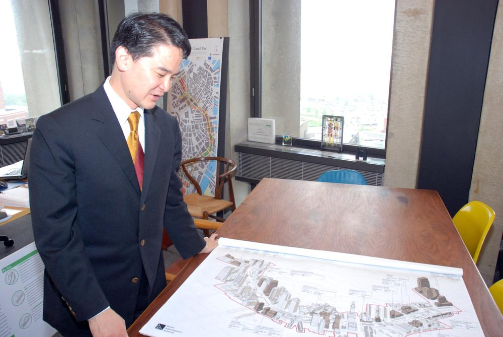 Kairos Shen, Boston's chief city planner, looks at plans for the Greenway in his City Hall office. (Lisa Tobin/WBUR)