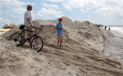 A father and son watch the cleanup of tar balls by oil cleanup workers in Dauphin Island, Ala., on Sunday, July 4th, 2010. City officials canceled their Fourth of July festivities because of the Deepwater Horizon oil spill. (AP)