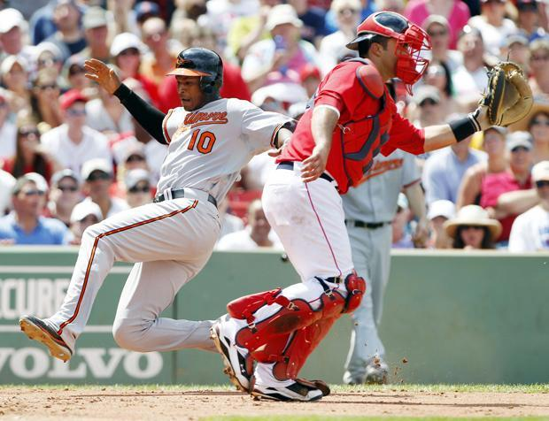 Baltimore's Adam Jones scores as Boston's Gustavo Molina waits for a throw in the fourth inning of the game on Sunday in Boston. (AP)