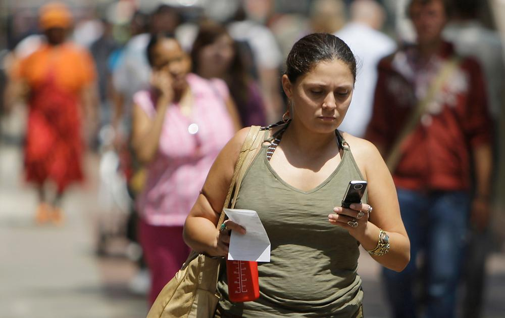 A woman sends text messages while walking through downtown Chicago. (AP)