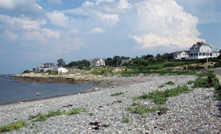 Houses overlook a pebbled beach in Cohasset. (Fred Thys/WBUR)