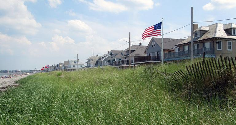Beach houses overlook tall grass in Hull. (Fred Thys/WBUR)
