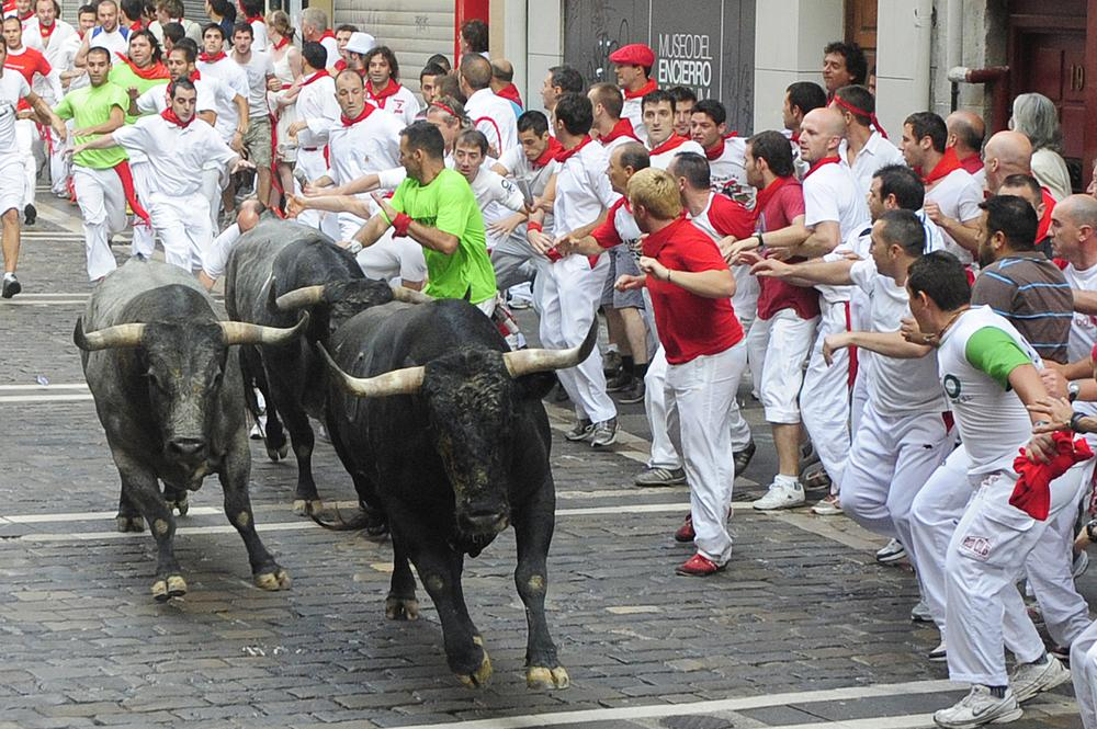 Revelers run next to Miura ranch fighting bulls during the fifth day of the running of the bulls at the San Fermin fiesta in Pamplona, Spain, Sunday. (AP Photo/Manu Fernandez)