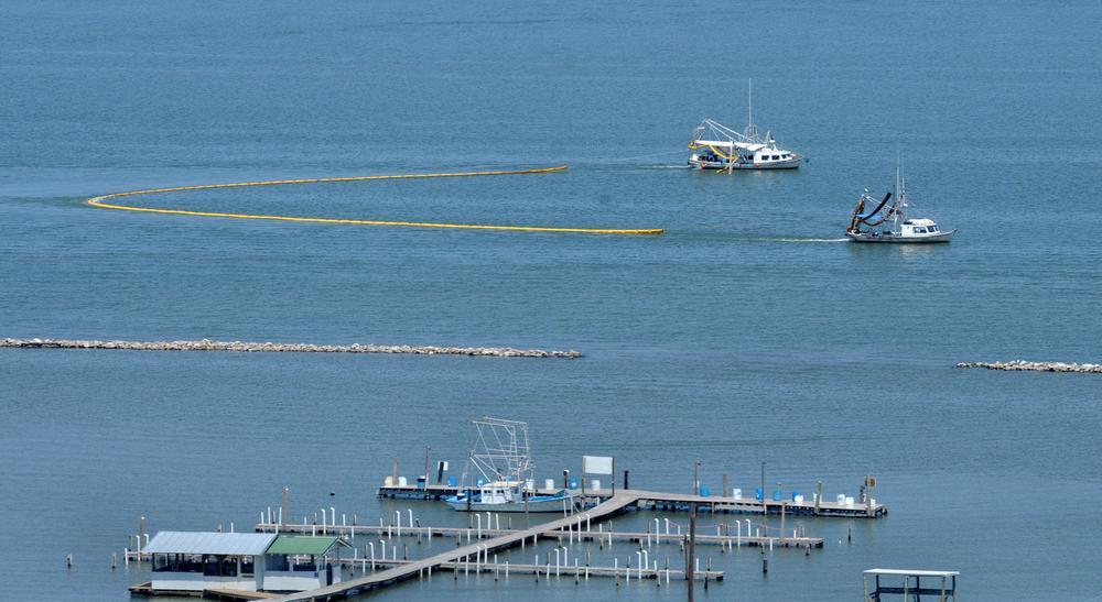 A pair of shrimp trawlers skim oil in Caminada Bay north of Grand Isle, La., Friday. (AP)