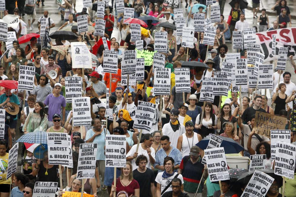 Protesters march during a rally against Arizona's immigration law, Saturday in Boston. Arizona Gov. Jan Brewer is attending the annual meeting of the National Governors Association this weekend in Boston. (AP Photo/Michael Dwyer)