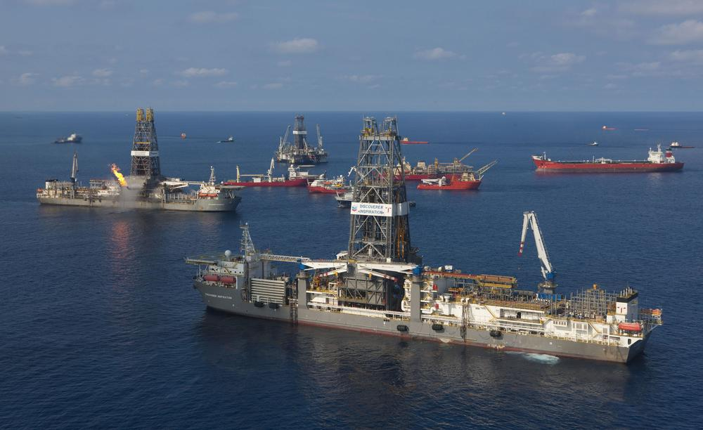 "The Transocean Discoverer Inspiration, foreground, arrives at the sight of the Deepwater Horizon to install a ""capping stack"" on the well Saturday, July 10, 2010 in the Gulf of Mexico. (AP Photo/BP, Marc Morrison)"