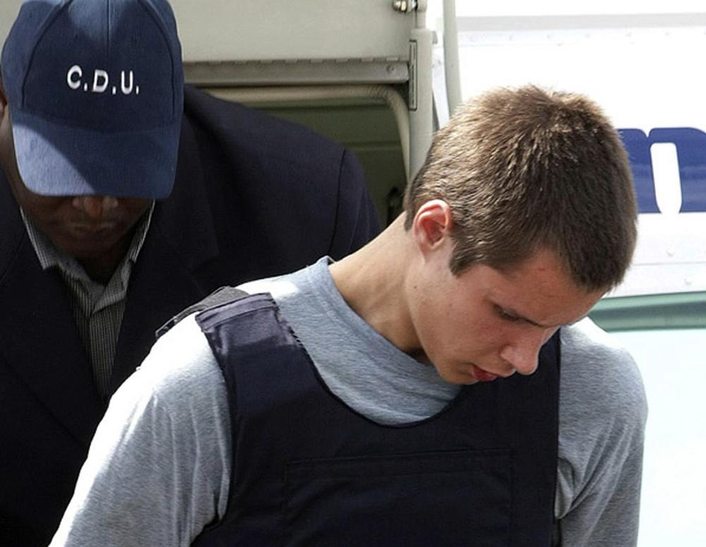 Colton Harris-Moore exits a plane handcuffed as he is escorted by police upon arrival to Nassau, Bahamas. (AP)