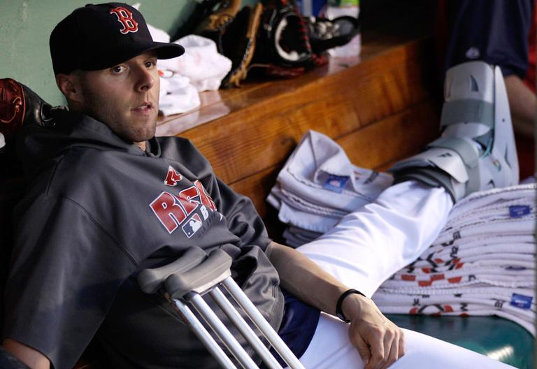 Boston Red Sox second baseman Dustin Pedroia rests his broken left foot in the dugout during a game on July 2. Pedroia says his foot doesn't require surgery and he hopes to return to the lineup soon. (AP)