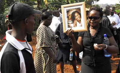 A relative carries a photograph during a burial ceremony for Alice Kyalimpa, one of dozens of people killed in the Sunday bomb blast in Wakiso, west of Uganda's capital city Kampala. (AP)