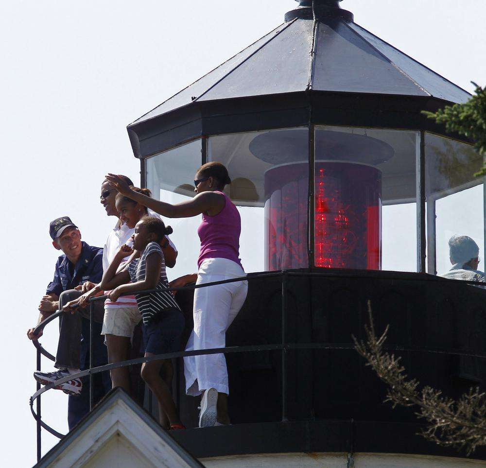 President Obama, first lady Michelle Obama, right, and daughters Malia and Sasha, center right, stand with Coast Guard Station chief Tim Chase, left, as they visit Bass Harbor Head Lighthouse in Bar Harbor, Maine, Saturday. (AP Photo/Charles Dharapak)