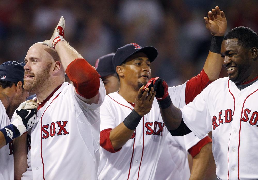 Kevin Youkilis, left, celebrates with teammates Eric Patterson, center, and David Ortiz, right, after hitting a sacrifice fly that allowed the winning run to score in the eleventh inning against the Rangers, Saturday, in Boston.  (AP Photo/Michael Dwyer)