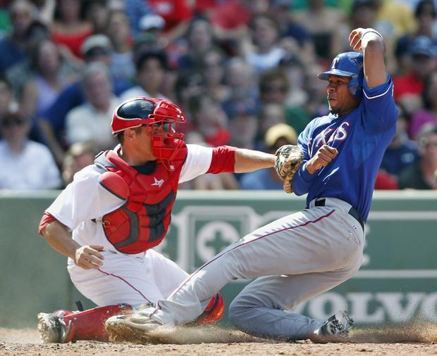 Texas' Elvis Andrus is safe at home plate as Boston's Kevin Cash puts the tag on in the eighth inning of the game on Sunday in Boston. The Rangers won 4-2. (AP)