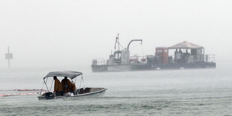 Oil cleanup workers skim for oil from the Deepwater Horizon oil spill in the Perdido Pass in Orange Beach, Ala., during a heavy rain storm on Sunday. (AP)