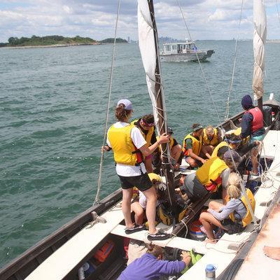 Instructor Jane Schenk helps the students disembark. (Jess Bidgood for WBUR)