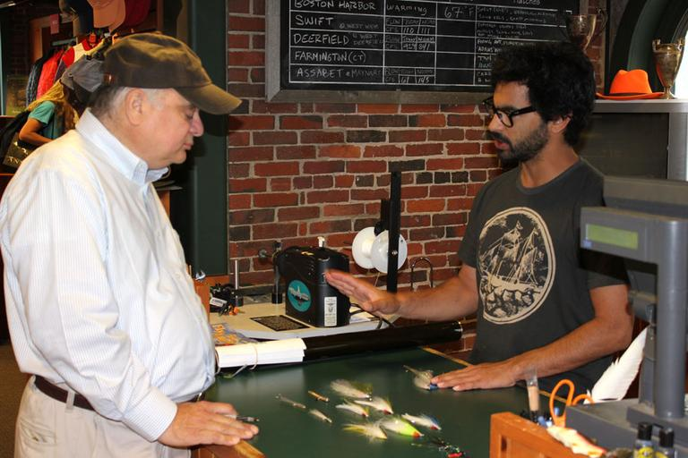 Stephen England, right, helps WBUR's Bob Oakes select the right fly for fishing Boston Harbor. (Lisa Tobin/WBUR)