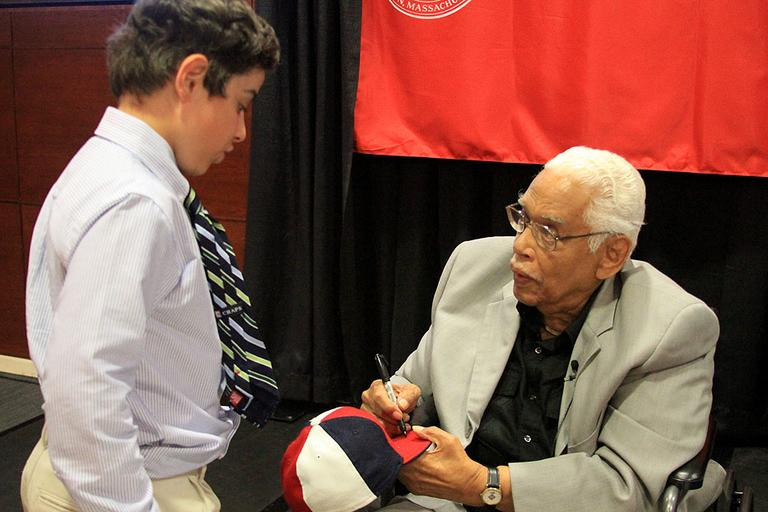 Former Negro League infielder Mahlon Duckett signs a young fan's hat at Northeastern. (Jeff Carpenter for WBUR)